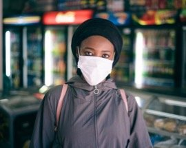 Black woman wearing face mask in grocery store.